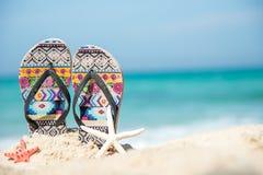 Chiuda sui sandali sulla spiaggia di sabbia con la spiaggia sabbiosa delle stelle marine Fotografia Stock Libera da Diritti