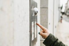 Chiuda sui torchi tipografici manuali femminili il bottone di doorphone La ragazza sta chiamando il citofono immagini stock