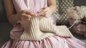 Chiuda sui vestiti di lana dei ferri da maglia delle mani della donna Hobby della donna archivi video