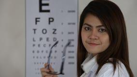 Chiuda sui vetri di usura di medico davanti al grafico di occhio archivi video