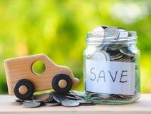 Chiuda sul barattolo delle monete e giochi l'automobile sulla tavola di legno sul fondo della sfuocatura, risparmiando i soldi pe immagine stock