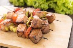 Chiuda sul barbecue sul tagliere di legno alla tavola Immagine Stock Libera da Diritti
