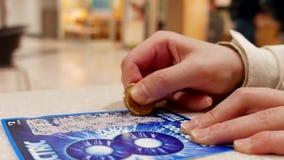 Chiuda sul biglietto di lotteria di scratch della donna chiamato elettrico video d archivio