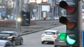 Chiuda sul cambiamento leggero del traffico cittadino urbano al verde dalle automobili rosse del segnale da continuare attraverso archivi video