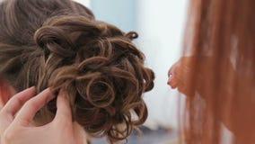 Chiuda sul colpo Acconciatura di rifinitura del parrucchiere per la giovane donna graziosa stock footage