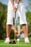 Chiuda sul colpo del giocatore di golf pronto a collocare sul tee fuori Fotografia Stock