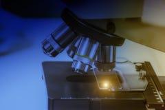 Chiuda sul colpo del microscopio alla presa del laboratorio con il ligh di arte fotografia stock