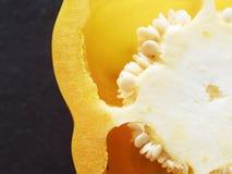 Chiuda sul colpo del seme, della placenta e del pericarpo del peperone dolce giallo o del capsico del taglio sopra fondo scuro Fotografia Stock Libera da Diritti
