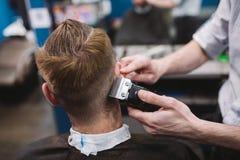 Chiuda sul colpo dell'uomo che ottiene il taglio di capelli d'avanguardia al negozio di barbiere Cliente maschio del servizio del immagini stock libere da diritti