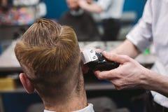 Chiuda sul colpo dell'uomo che ottiene il taglio di capelli d'avanguardia al negozio di barbiere Cliente maschio del servizio del immagine stock