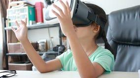 Chiuda sul colpo della bambina asiatica che usando i vetri di realtà virtuale sulla tavola stock footage