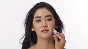 Chiuda sul colpo della donna asiatica attraente che ottiene un comporre dal truccatore professionista stock footage