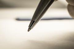 Chiuda sul colpo della mano di un uomo che tiene una penna a sfera sul wh Fotografie Stock