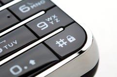Chiuda sul colpo della tastiera mobile nell'ambito di indicatore luminoso Fotografie Stock
