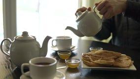 Chiuda sul colpo delle mani del ` s dell'uomo, che versa il tè da una teiera della porcellana stock footage