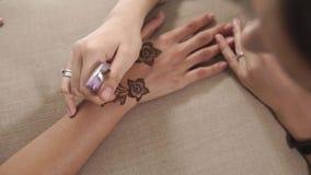 Chiuda sul colpo delle mani del ` una s della donna, che è olio d'idratazione applicato sul mehendi video d archivio
