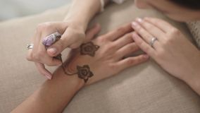 Chiuda sul colpo delle mani del ` una s della donna, che ha un mehendi sul suoi polso e dita video d archivio