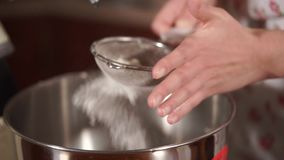 Chiuda sul colpo delle mani del ` una s della donna, che vaglia la farina al un setaccio nel miscelatore archivi video
