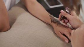 Chiuda sul colpo delle mani del ` una s della donna, su una mano suntanned applicano la pittura per disegnare Mendy archivi video