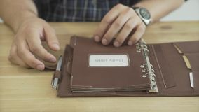 Chiuda sul colpo delle mani dell'uomo che aprono il giornale quotidiano del pianificatore del cuscinetto di cuoio marrone chiaro  archivi video