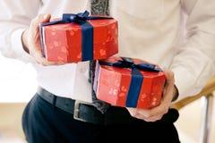 Chiuda sul colpo delle mani dell'uomo d'affari che giudicano i contenitori di regalo luminosi avvolti con il nastro blu Natale, n fotografia stock libera da diritti