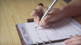 Chiuda sul colpo delle mani della donna che scrivono con la penna d'argento in giornale di cuoio marrone della pallottola dell'in stock footage
