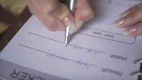 Chiuda sul colpo delle mani della donna che scrivono con la penna d'argento nel pianificatore di cuoio marrone del giornale della archivi video