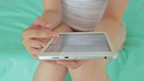 Chiuda sul colpo delle mani della donna s che fanno scorrere il testo sulla compressa digitale stock footage