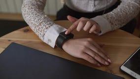 Chiuda sul colpo delle mani di una signora di affari, che utilizza gli orologi astuti per osservare i messaggi video d archivio