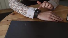 Chiuda sul colpo delle mani di una signora di affari, che utilizza gli orologi astuti per osservare i messaggi archivi video