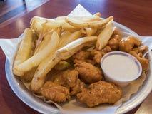Chiuda sul colpo delle patate fritte e delle ali di pollo piccanti Fotografia Stock
