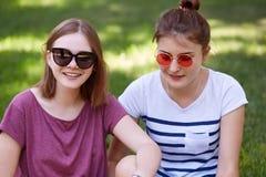 Chiuda sul colpo di bello recreat delle sorelle durante il giorno soleggiato all'aperto, indossi le tonalità e le magliette casua fotografie stock libere da diritti