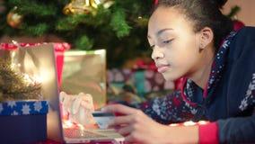 Chiuda sul colpo di giovane donna di colore che compera online sulla notte di Natale archivi video