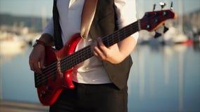 Chiuda sul colpo di un basso elettrico giocato da un musicista sulla via di giorno archivi video