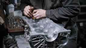 Chiuda sul colpo di un blocco motore di smontaggio del meccanico professionista nel centro di manutenzione dell'automobile video d archivio