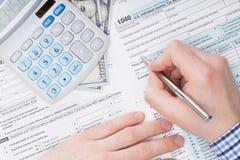 Chiuda sul colpo di un maschio che compila la forma di imposta degli Stati Uniti 1040 accanto al calcolatore ed a 100 dollari di  Fotografie Stock