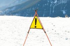 Chiuda sul colpo di un segnale di pericolo ad un pendio di una stazione sciistica Immagine Stock