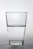 Chiuda sul colpo di un vetro di acqua pieno a metà Immagini Stock Libere da Diritti