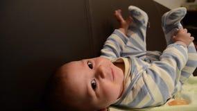 Chiuda sul colpo sopraelevato del neonato sul soffa che gioca con i suoi piedi stock footage