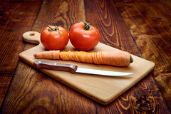 Chiuda sul coltello e sul pomodoro sulla tavola di legno immagine stock