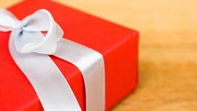 Chiuda sul contenitore di regalo rosso con il nastro bianco sul fondo di legno della tavola con lo spazio della copia Fotografia Stock