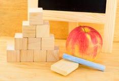 Chiuda sul cubo rosso di legno e della mela nell'allineamento della piramide con gesso Immagine Stock