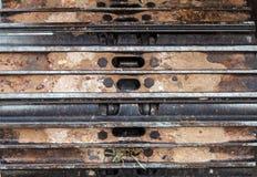 Chiuda sul frammento del trattore a cingoli e sporchi il fondo Fotografie Stock