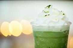 Chiuda sul frappe del tè verde con il fondo leggero del bokeh fotografie stock
