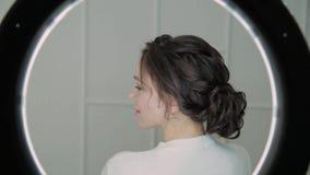 Chiuda sul fronte castana seducente della donna con capelli soffiati aria, esaminanti la macchina fotografica Ring Light Beauty stock footage