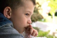 Chiuda sul fronte del ragazzo di 5 anni che guarda fuori la finestra Immagini Stock