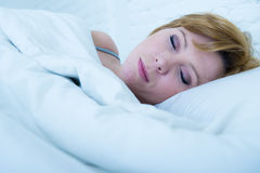 Chiuda sul fronte di giovane donna attraente con capelli rossi che dorme pacificamente trovandosi a letto a casa Fotografie Stock