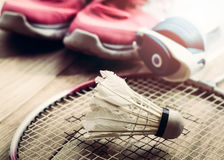 Chiuda sul gallo della navetta sulla racchetta con le scarpe da tennis e la bottiglia di acqua Fotografie Stock