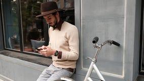 Chiuda sul giovane in abbigliamento casual con Internet praticante il surfing della bicicletta sullo smartphone archivi video