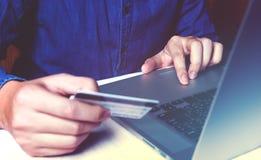 Chiuda sul giovane asiatico che per mezzo del computer portatile e tenendo i wi della carta di credito Fotografie Stock